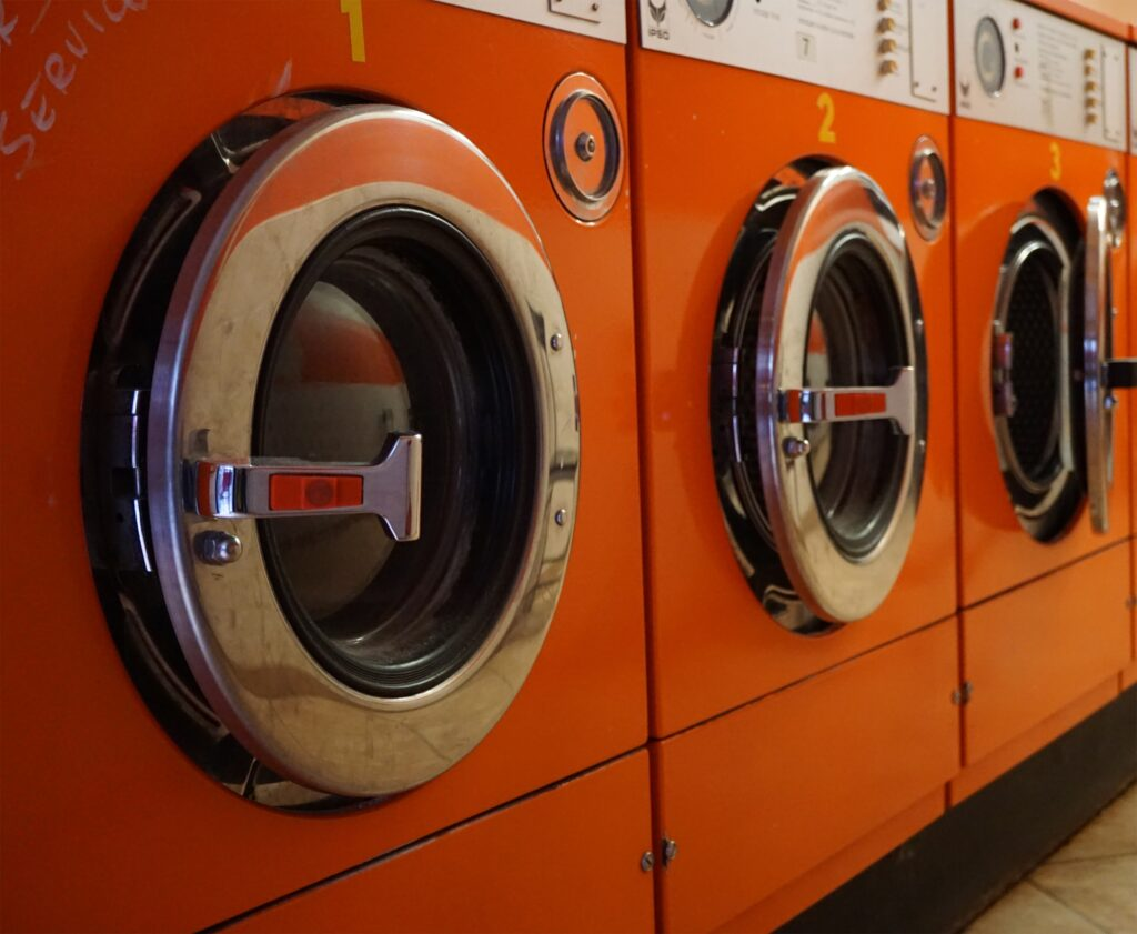 "A row of orange industrial washing machines in a laundromat - <span>Photo by <a href=""https://unsplash.com/@tinabosse8?utm_source=unsplash&utm_medium=referral&utm_content=creditCopyText"">Tina Bosse</a> on <a href=""https://unsplash.com/s/photos/laundry?utm_source=unsplash&utm_medium=referral&utm_content=creditCopyText"">Unsplash</a></span>"
