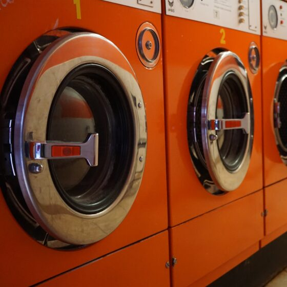 A row of orange industrial washing machines in a laundromat - Photo by Tina Bosse on Unsplash